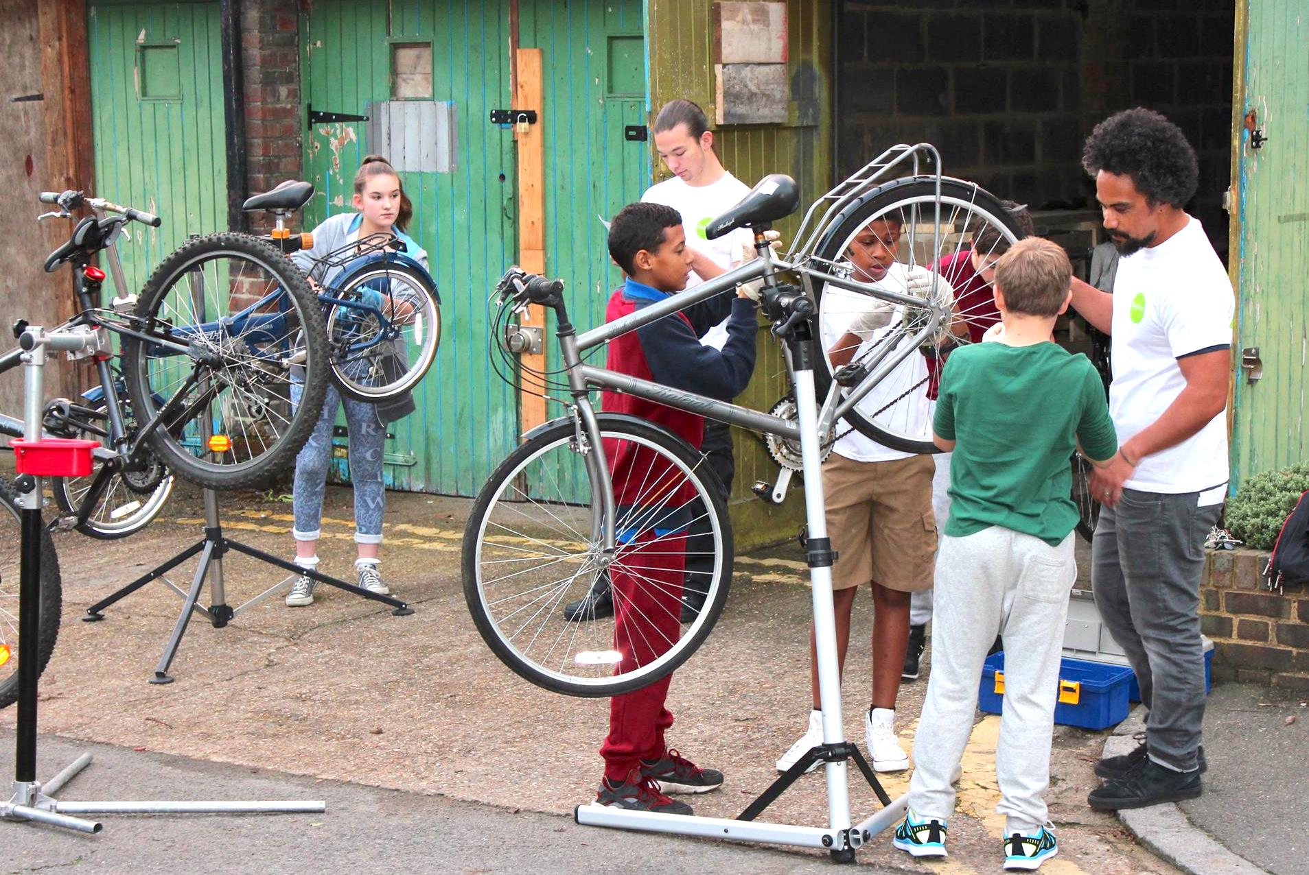 Young people learning how to fix bikes
