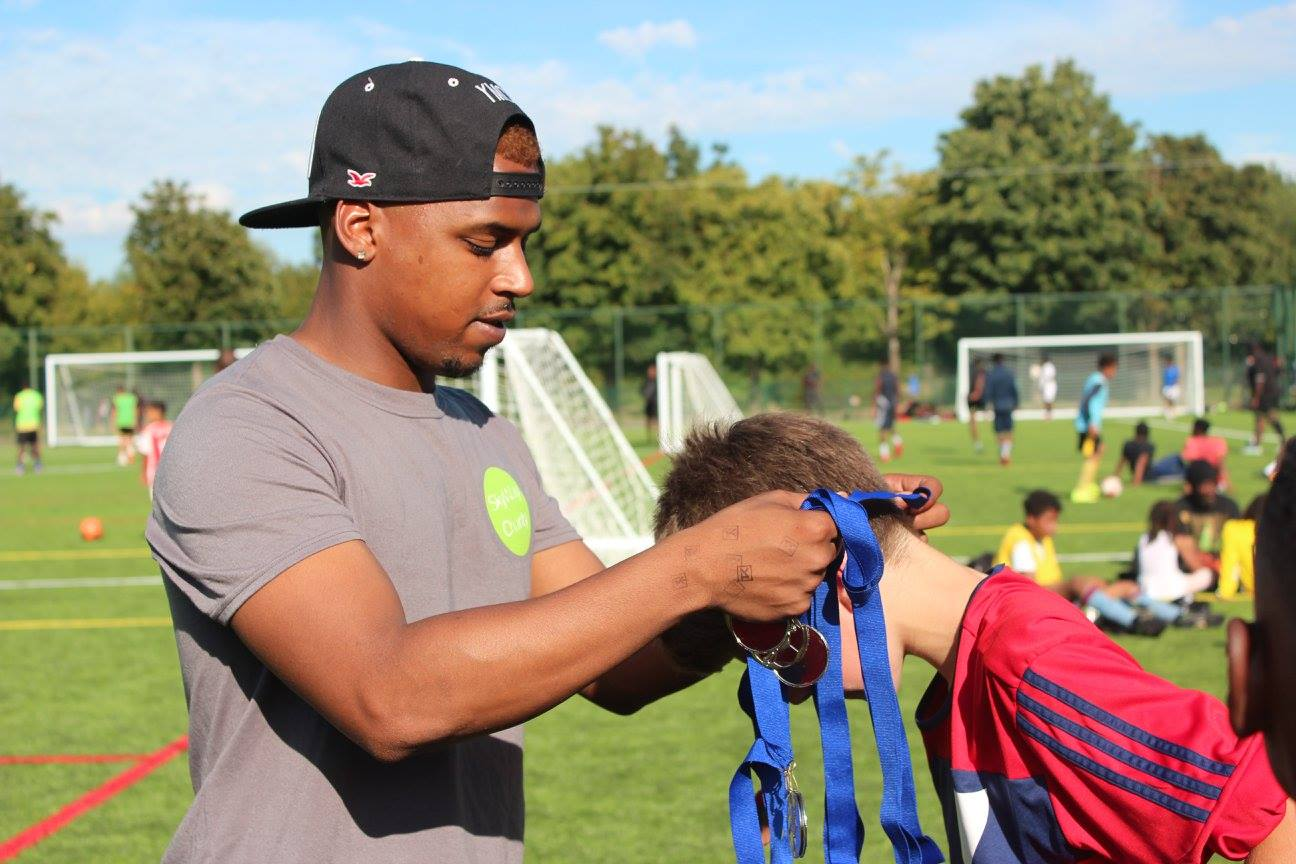 Member of the team putting a medal on a boy