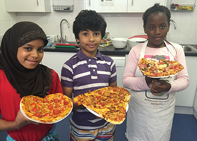 Three young people holding up their pizza