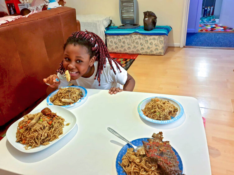 Young girl eating a meal that she's prepared as part of the weekend meal challenge