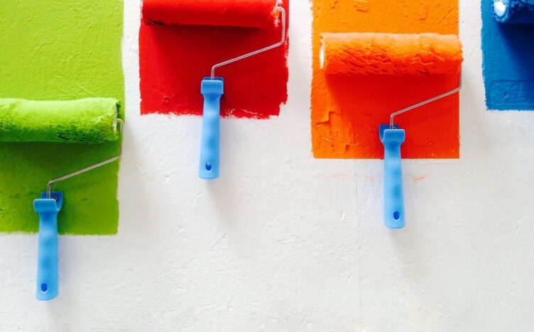 Green, red, yellow and blue pain rollers on a white wall