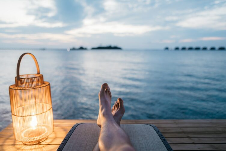 Shot of mans legs as he relaxes laying down with a view of the ocean ahead of him