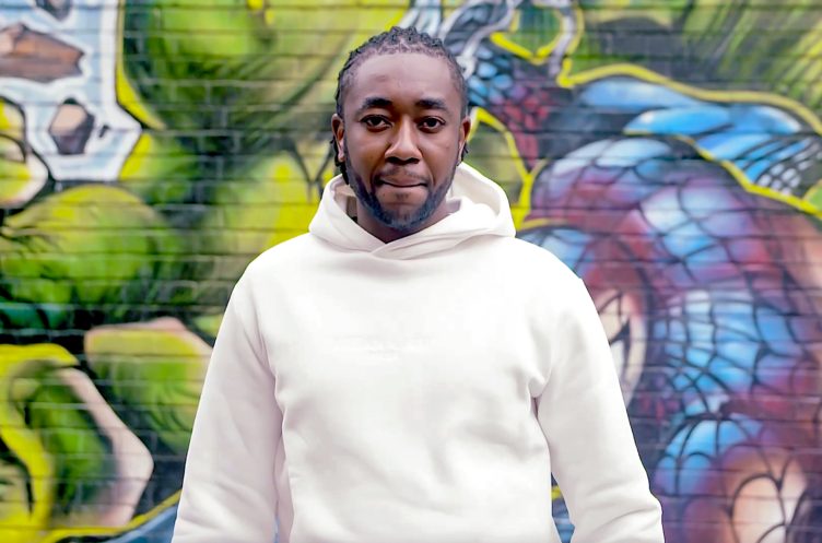 Joshua (25), our newest trustee and a successful entrepreneur standing in front of a graffiti painted brick wall